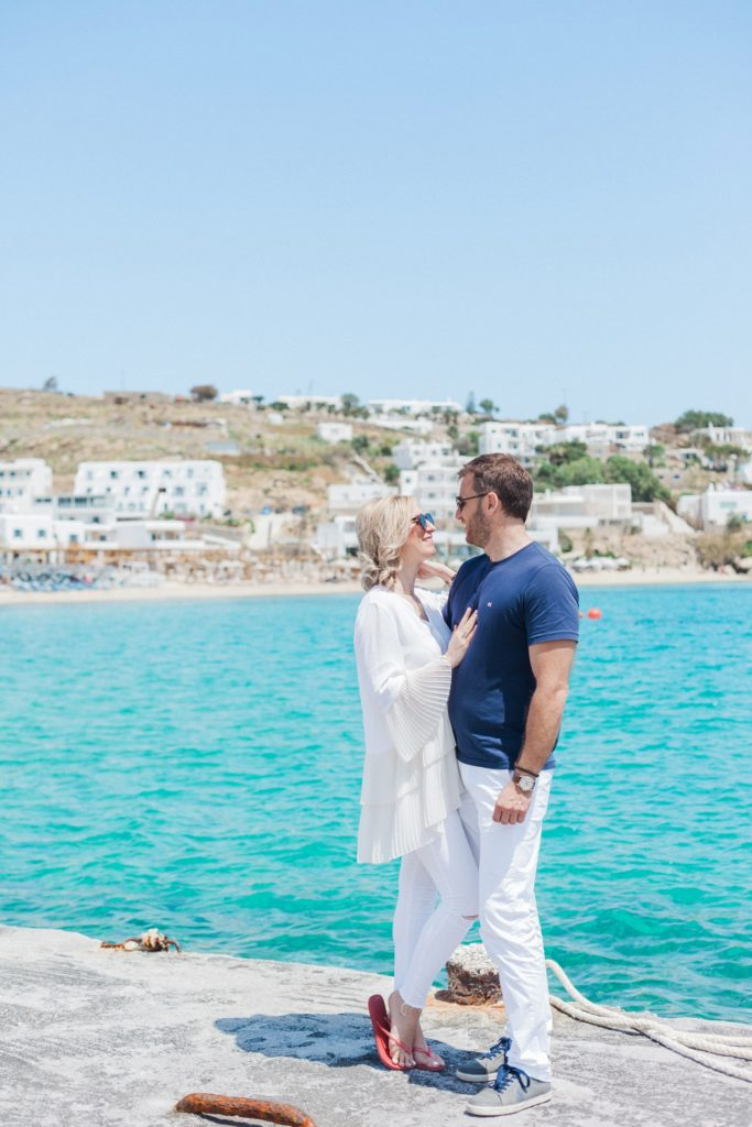 Couple stand near the sea with a view of Platis Yialos beach on Mykonos behind them