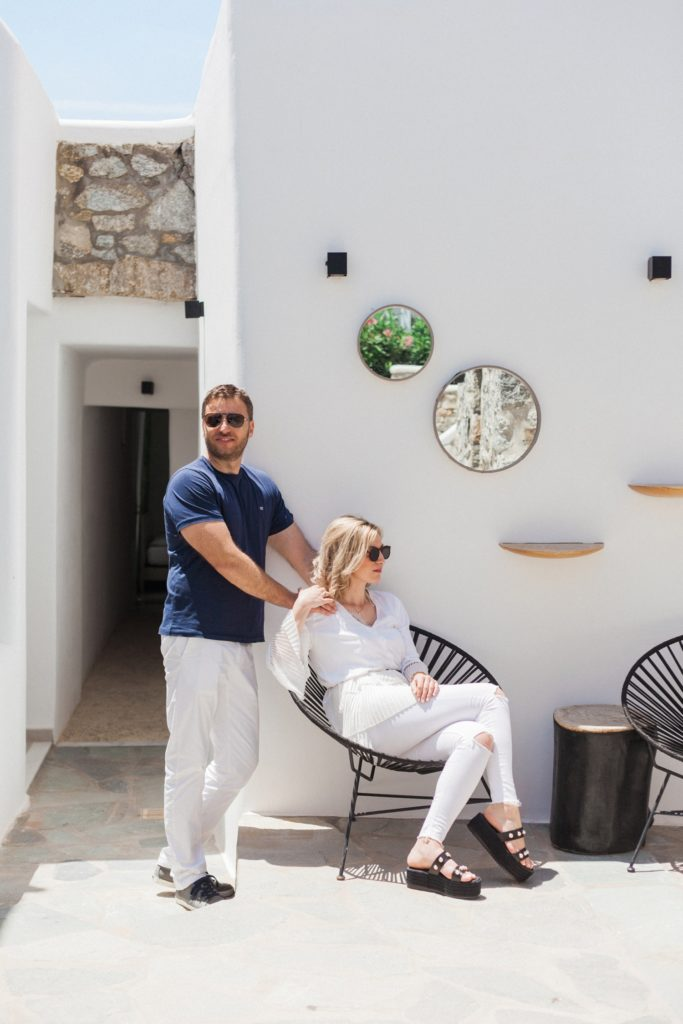 Couple pose against a white wall at Artemoulas Studios Mykonos
