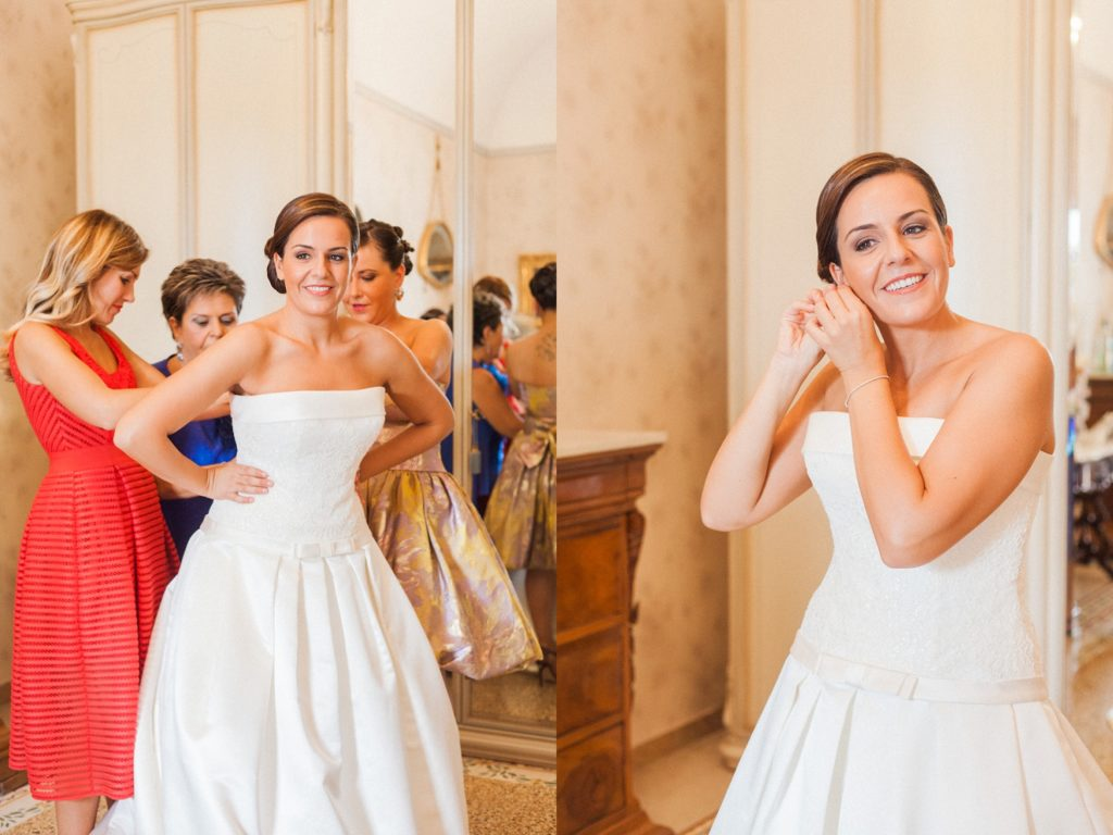 Mother-of-the-bride and close friends help to get the bride into her corset on the morning of her wedding in Abruzzo