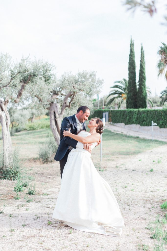 The groom dips the bride as they dance in the gardens of the Convivium Hotel in Vasto during their Abruzzo wedding
