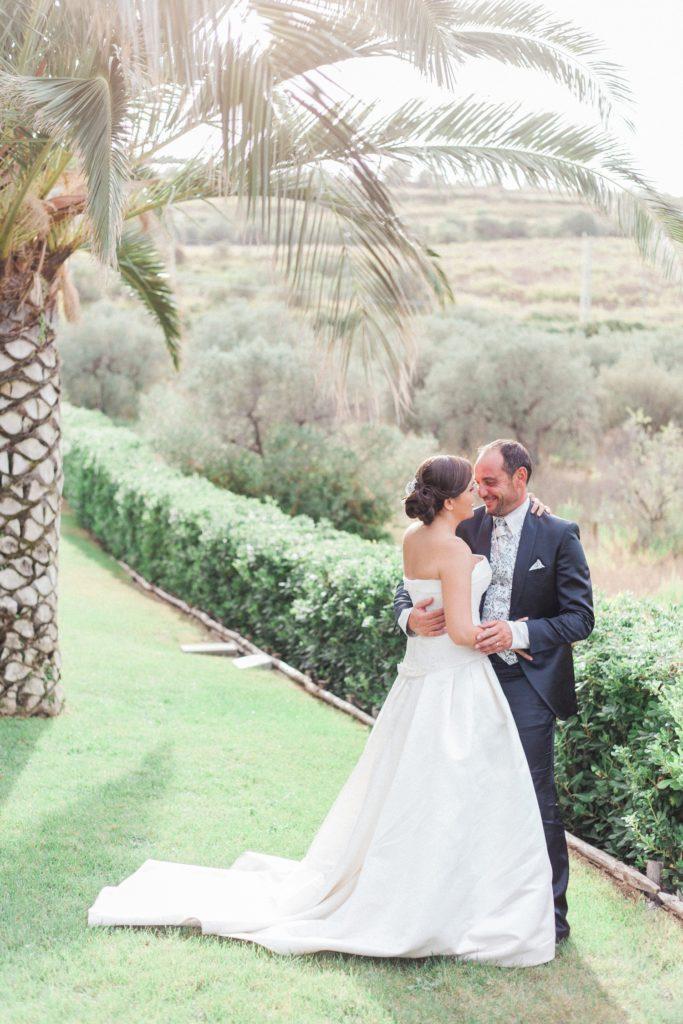 Couple hug under a palm tree at the Convivium Hotel in Vasto