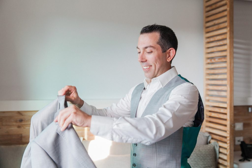 Groom smiles as he dresses in a Ted Baker suit on his wedding day