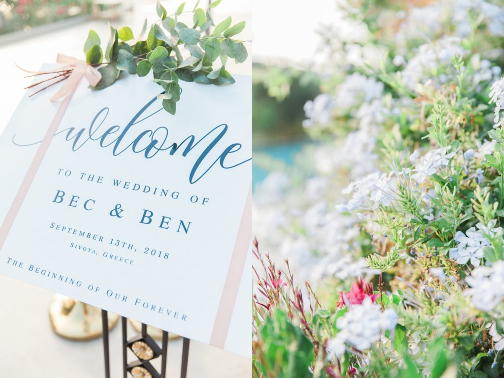 Wedding welcome sign next to flowers by the pool at Domotel Agios Nikolaos in Sivota