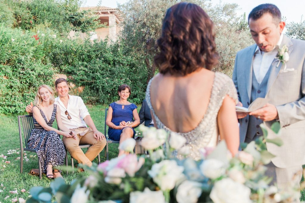 Guests smile as couple exchange vows during their destination wedding ceremony