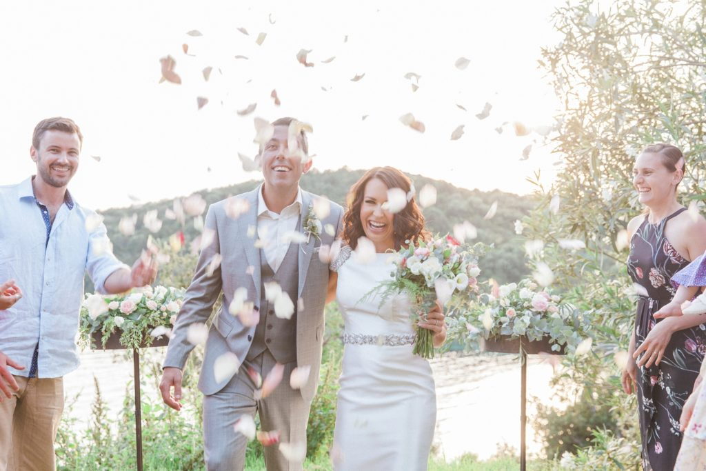 Couple smile as their guests shower them with confetti