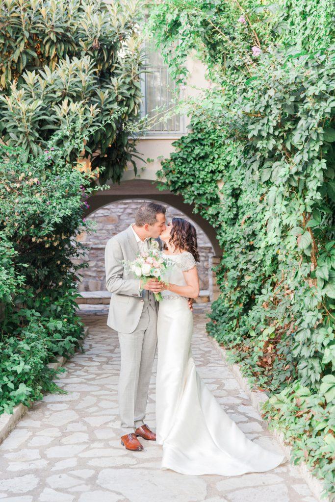 Couple kiss during their wedding portrait session at Domotel Agios Nikolaos in Sivota