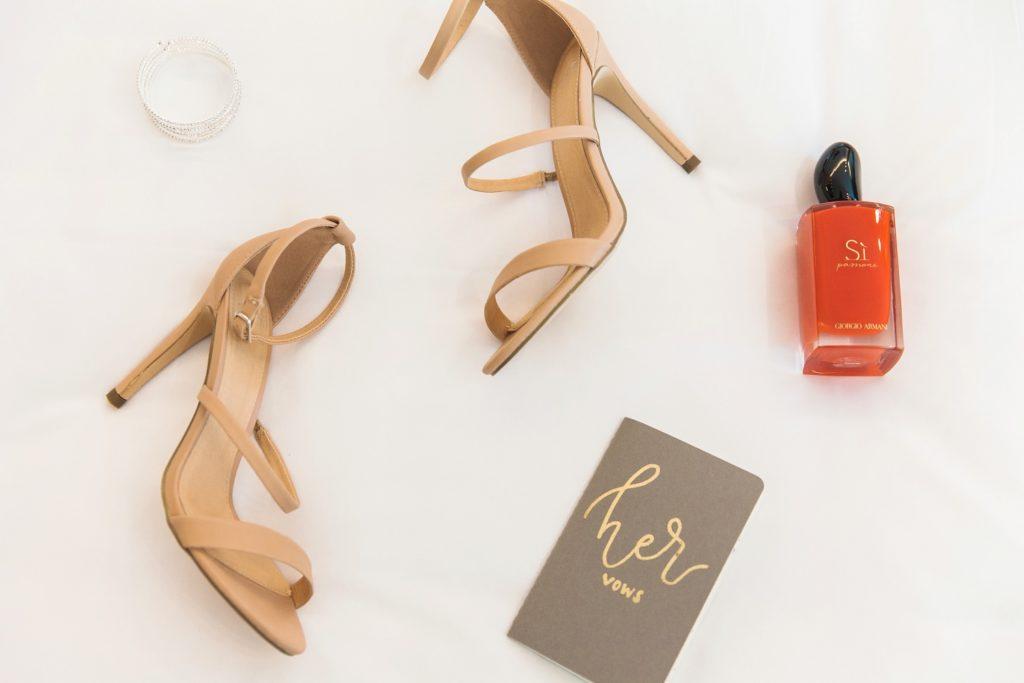 Flat lay of brides details including Carvella heels, vow book, diamond bracelet and Armani fragrance