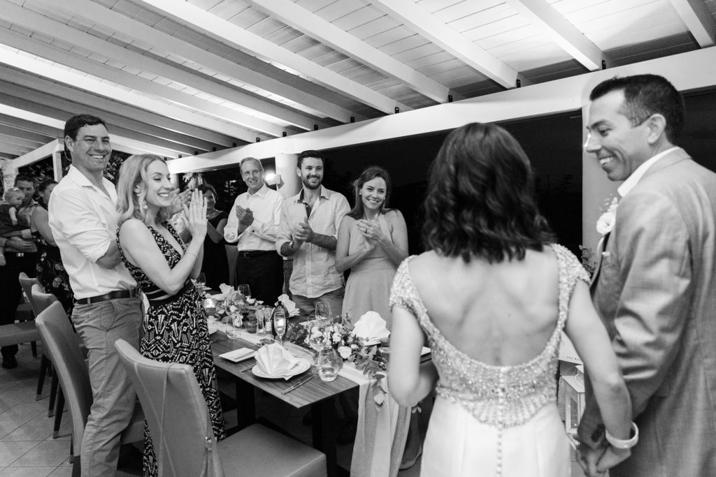 Guests stand clapping as the bride and groom arrive at their wedding reception
