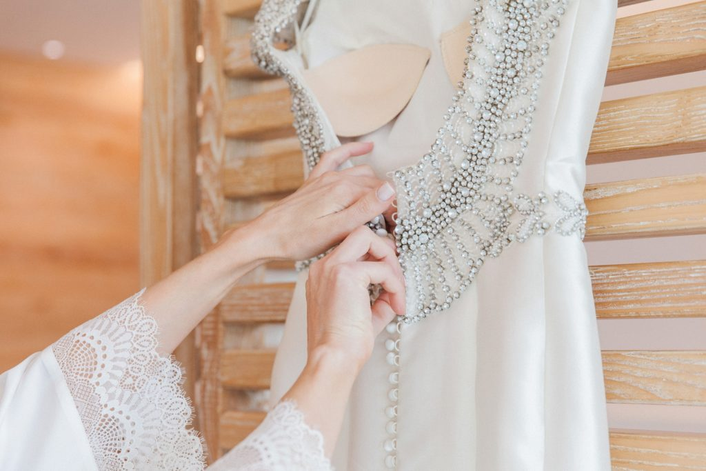Bride undoes the buttons on her Rosa Clara wedding dress before putting it on
