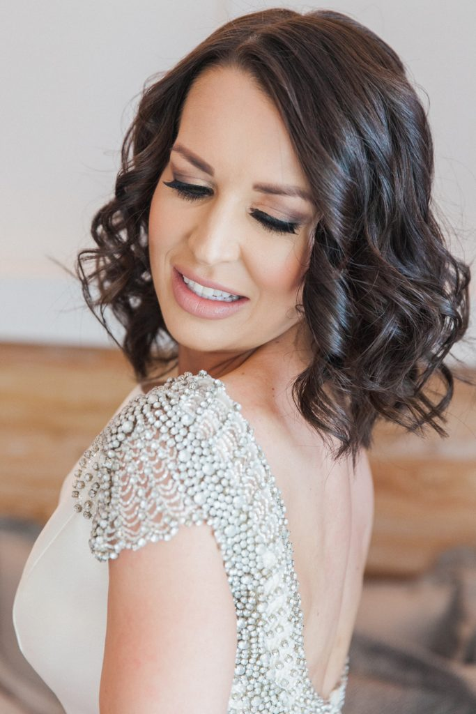Bride looks over her shoulder as a friend does up the buttons on her wedding dress