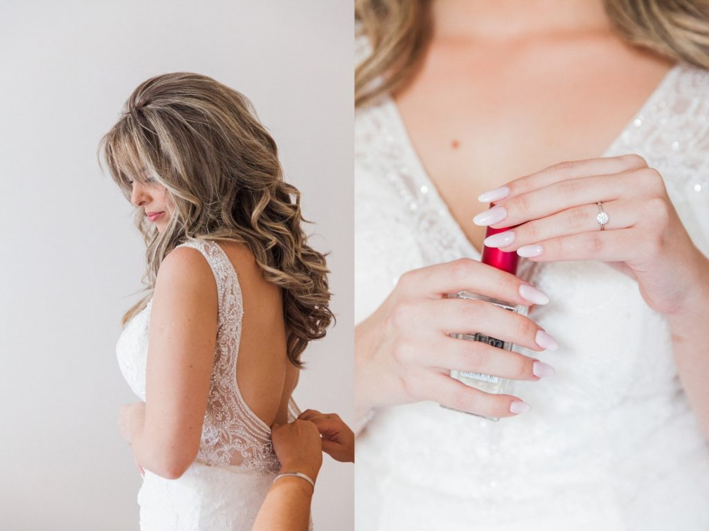 Bride putting on her dress and holding her perfume on the morning of her wedding