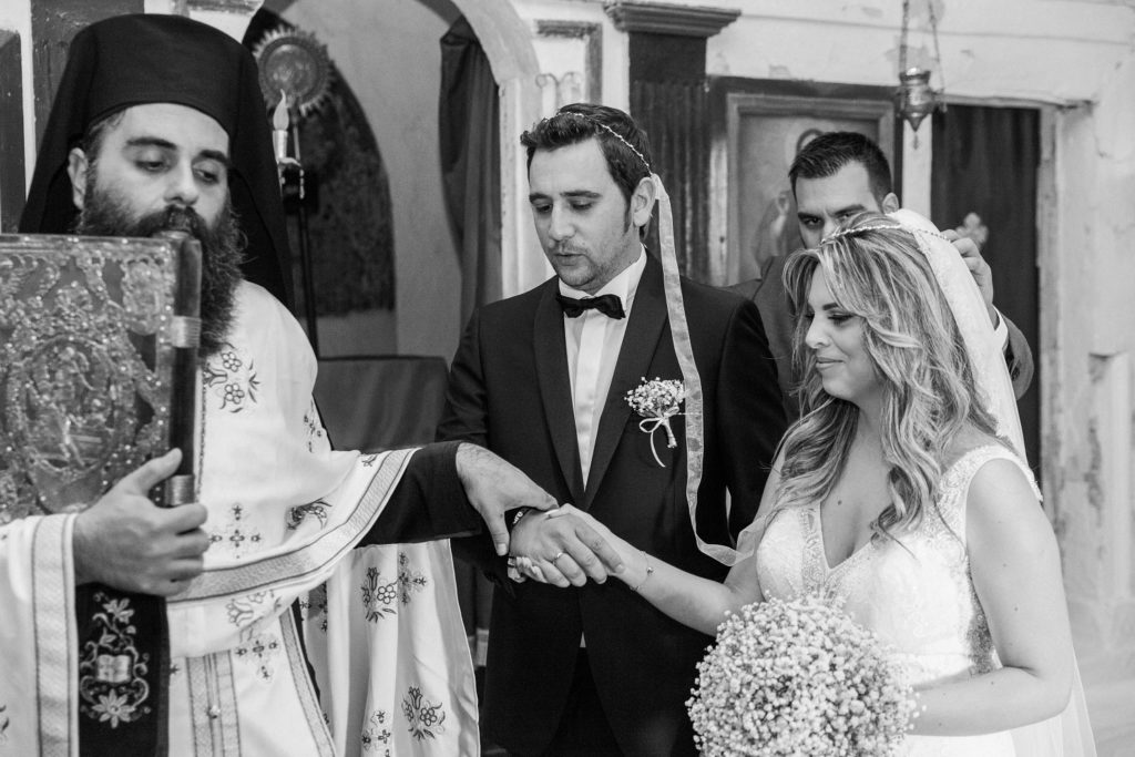 Bride ang groom make their way around the alter during their Greek wedding ceremony