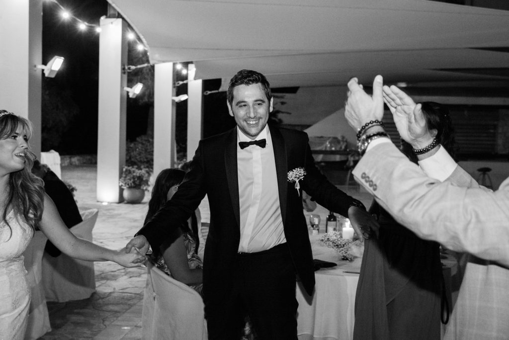 Groom smiles during the traditional Greek dancing at his Ionian Blue Hotel wedding on Lefkada