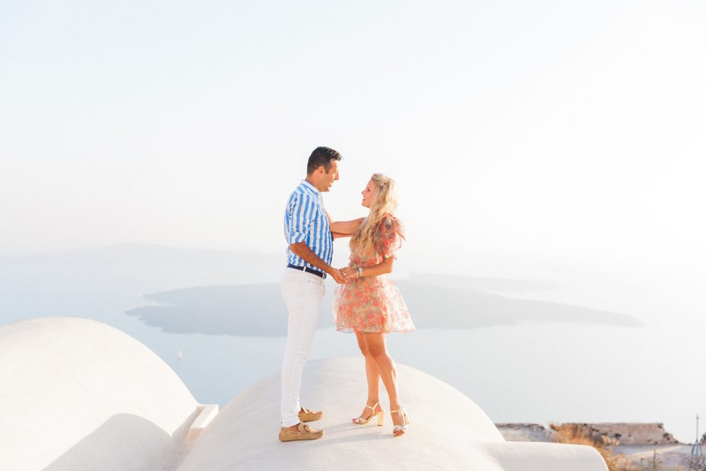 Happy couple stand on a domed roof of a cave house in Santorini