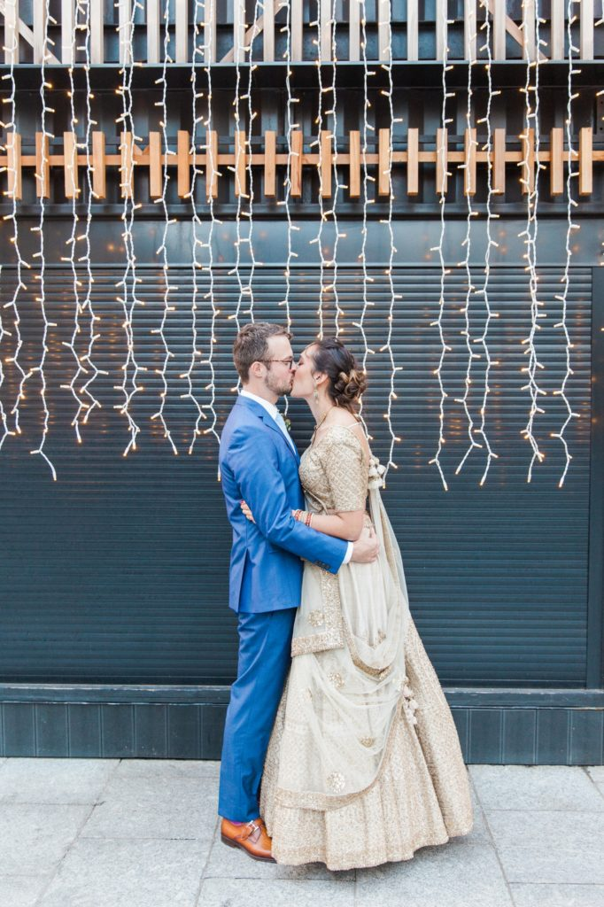 Bride and groom kiss against a backdrop of fairy lights in London