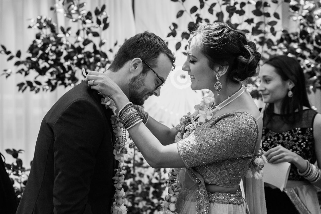 Bride places a flower mala over her groom during their South Place Hotel wedding