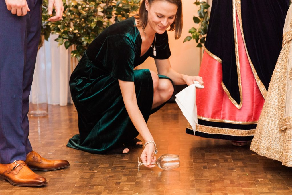 Grooms sister places a wine glass on the floor during a Jewish-Indian mixed culture wedding ceremony