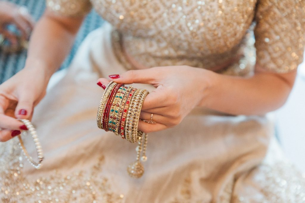 Indian bride putting on her bangles on the morning of her South Place Hotel wedding