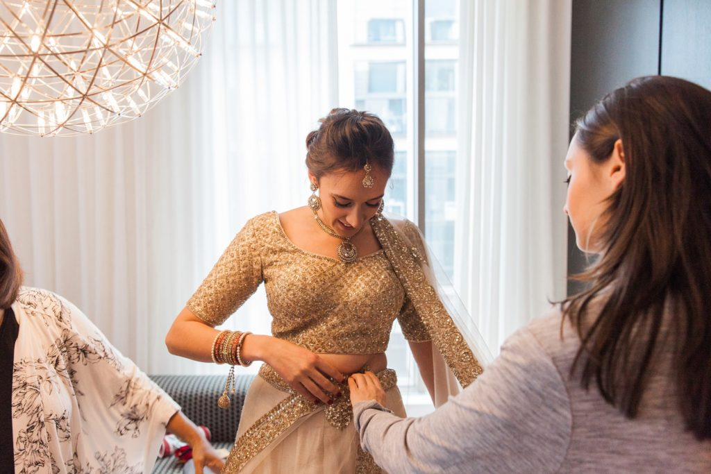 Bride getting helped into her gold lehenga on the morning of her South Place Hotel wedding in London