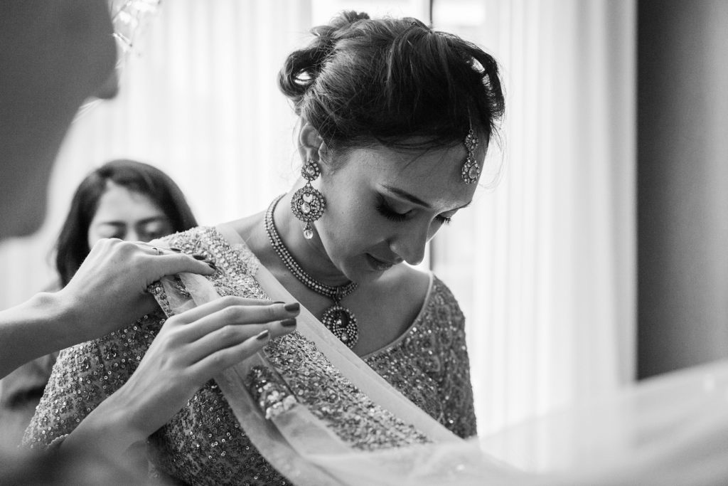 Indian bride being helped into her gold lehenga on the morning of her South Place Hotel wedding