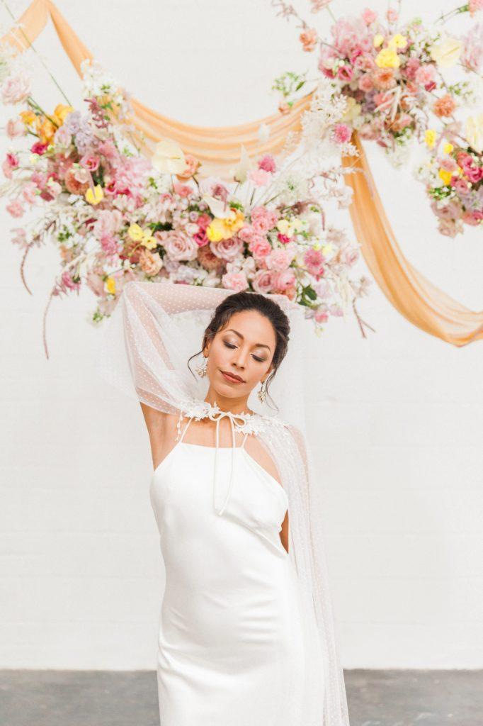 Portrait of a black bride in a Halfpenny London wedding dress below colourful hanging flower arrangements
