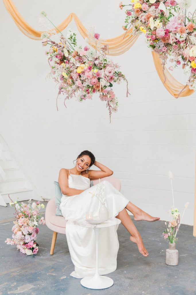 Happy bride sits with her feet up under a hanging spring flower cloud on her wedding day