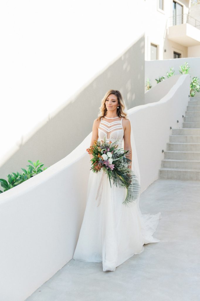 Bride in an ivory Atelier Zolotas wedding gown walking through Crystal Waters Lefkada