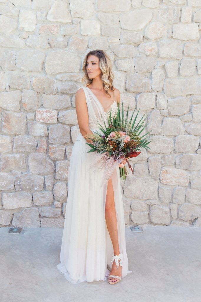 Bride poses in an Atelier Zolotas wedding dress and boho bridal bouquet