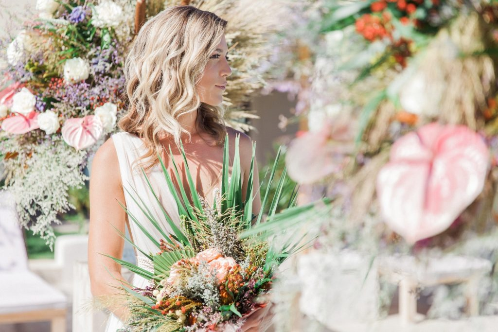 Bride wearing an Atelier Zolotas wedding dress with pastel and grass floral arrangements at Crystal Waters Lefkada