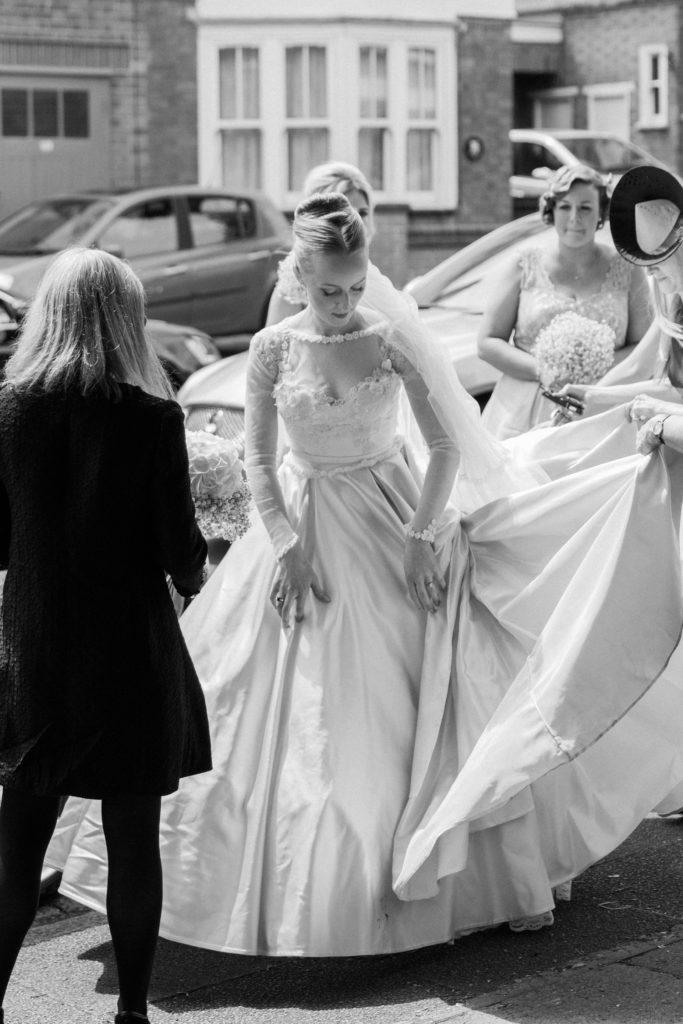 Bride arranges her blush pink wedding gown as she gets out of the car on the morning of her wedding