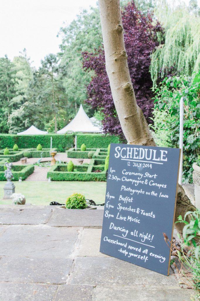 Wedding schedule on a chalk board in the garden in Leicestshire