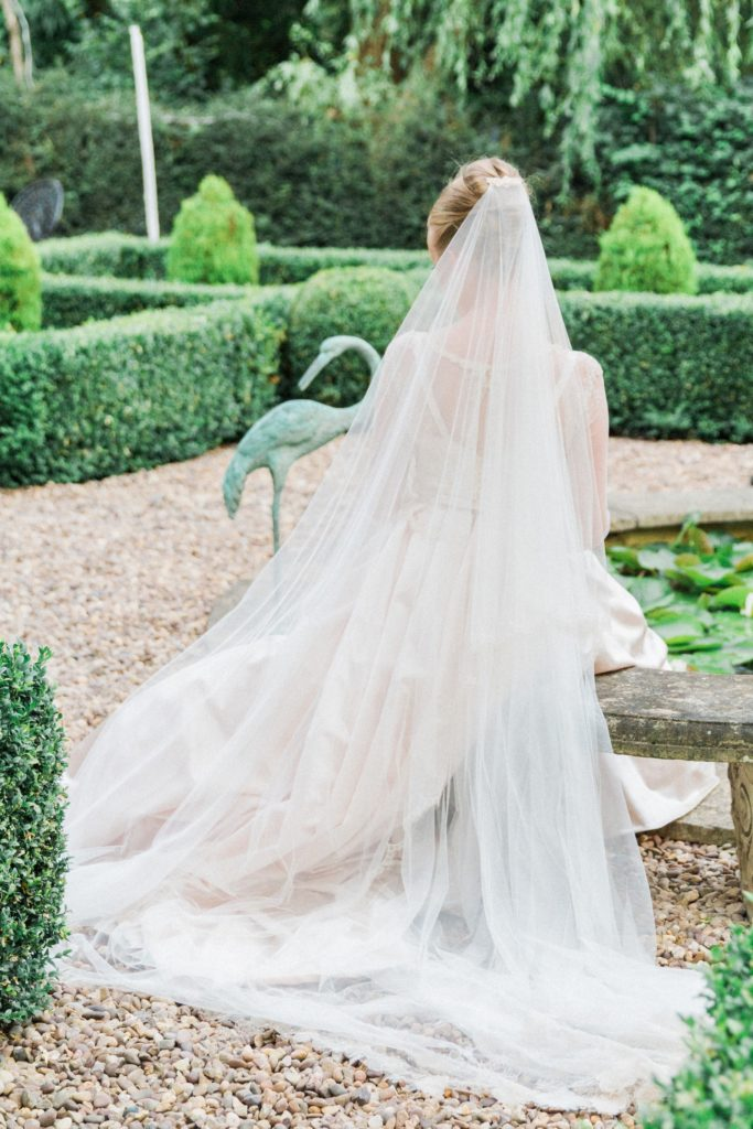 Bride sits next to the pond during her English garden wedding
