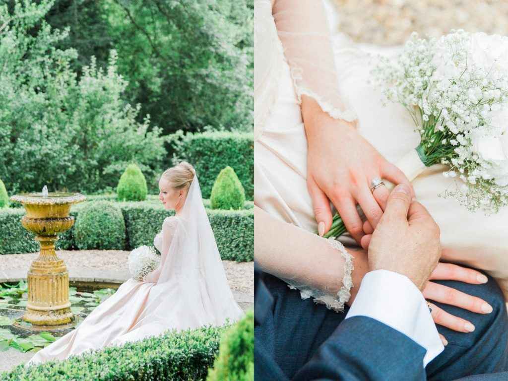 Bride and groom hold hands showing her diamond ring during their English garden wedding