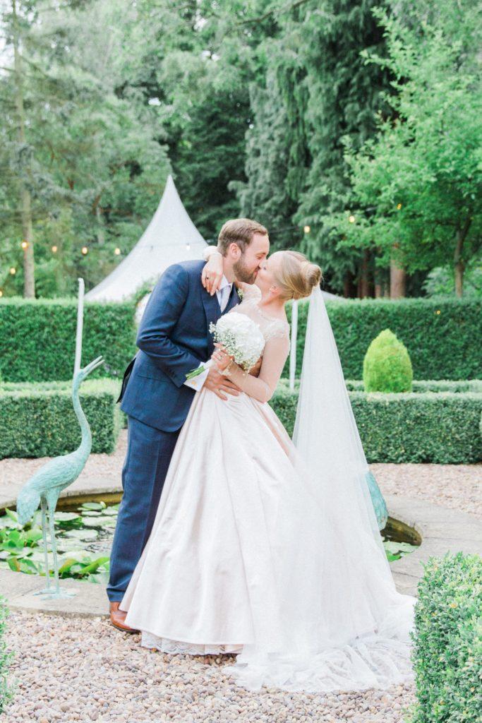 Couple kiss next to a fountain during their English garden wedding