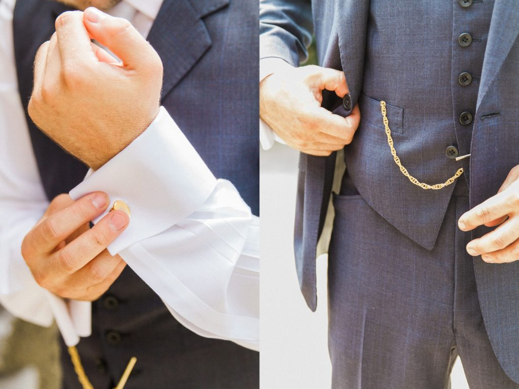 Groom fastens his cufflinks and jacket buttons