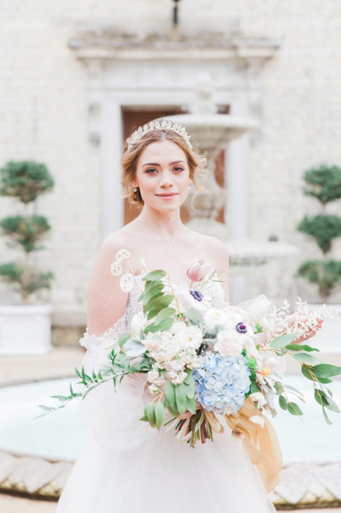 Portrait of a bride holding a pastel free-flowing bouquet in front of Froyle Park wedding venue