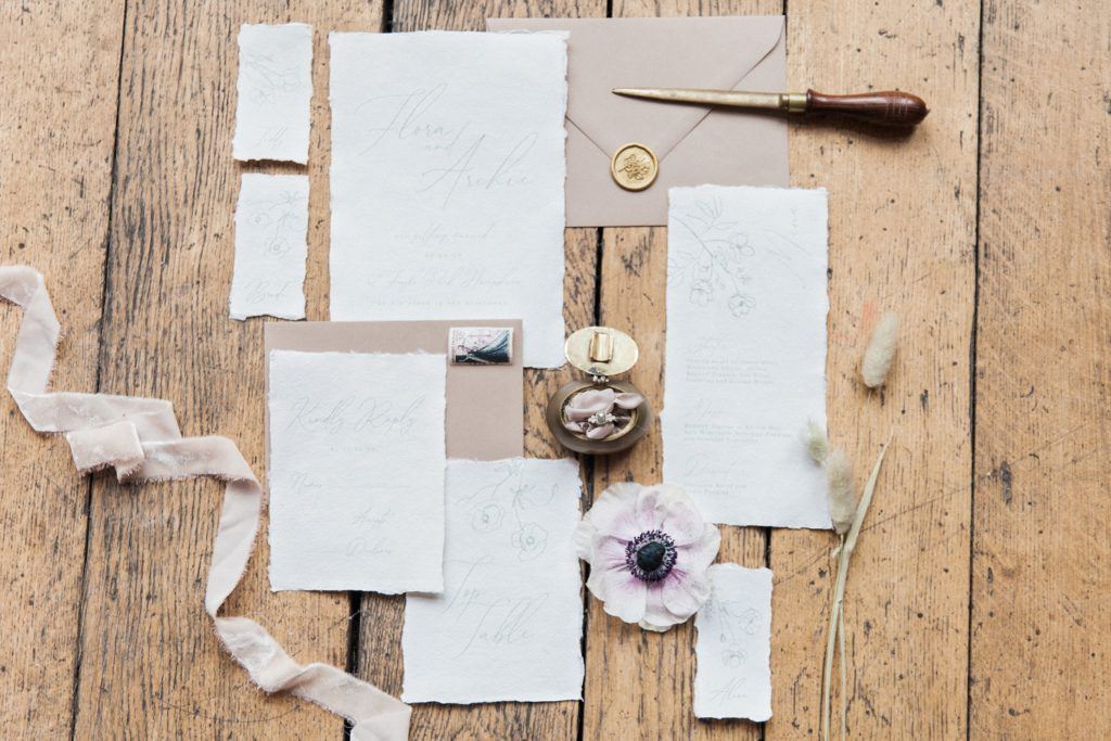 Flatlay of wedding stationery by Abbie Worton Design in neutral colours