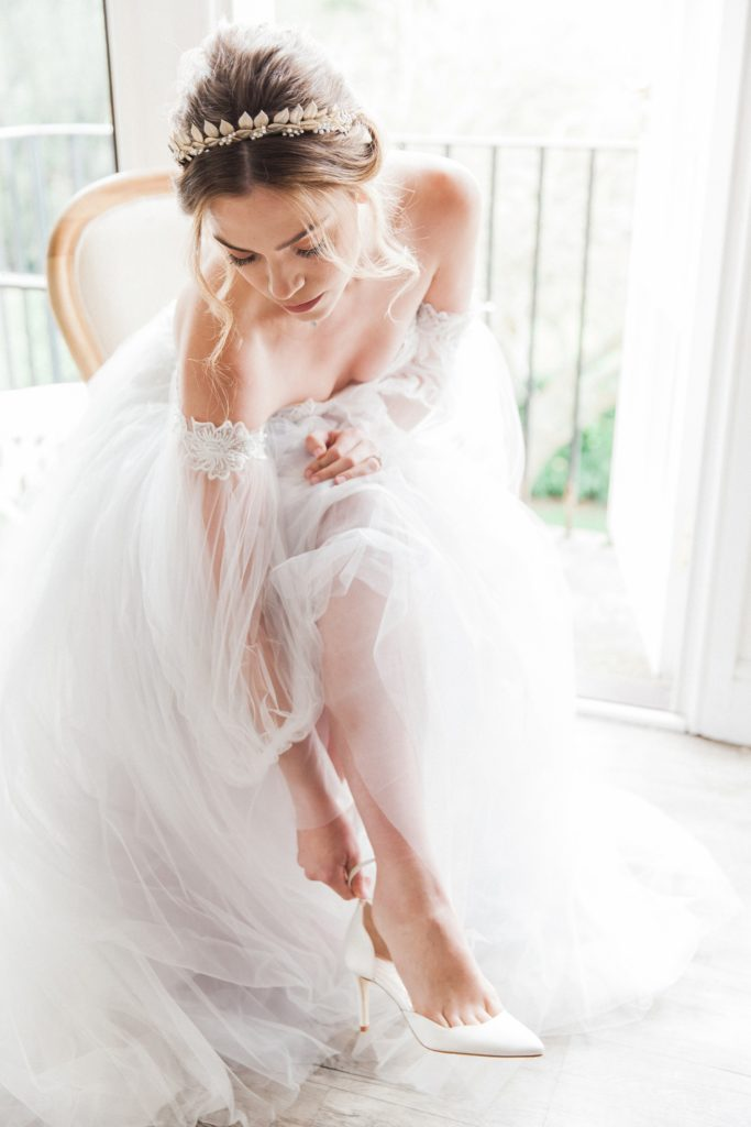 Bride puts on her Harriet Wilde shoes while wearing a Chic Nostalgia wedding dress from Hannah Elizabeth Bridal