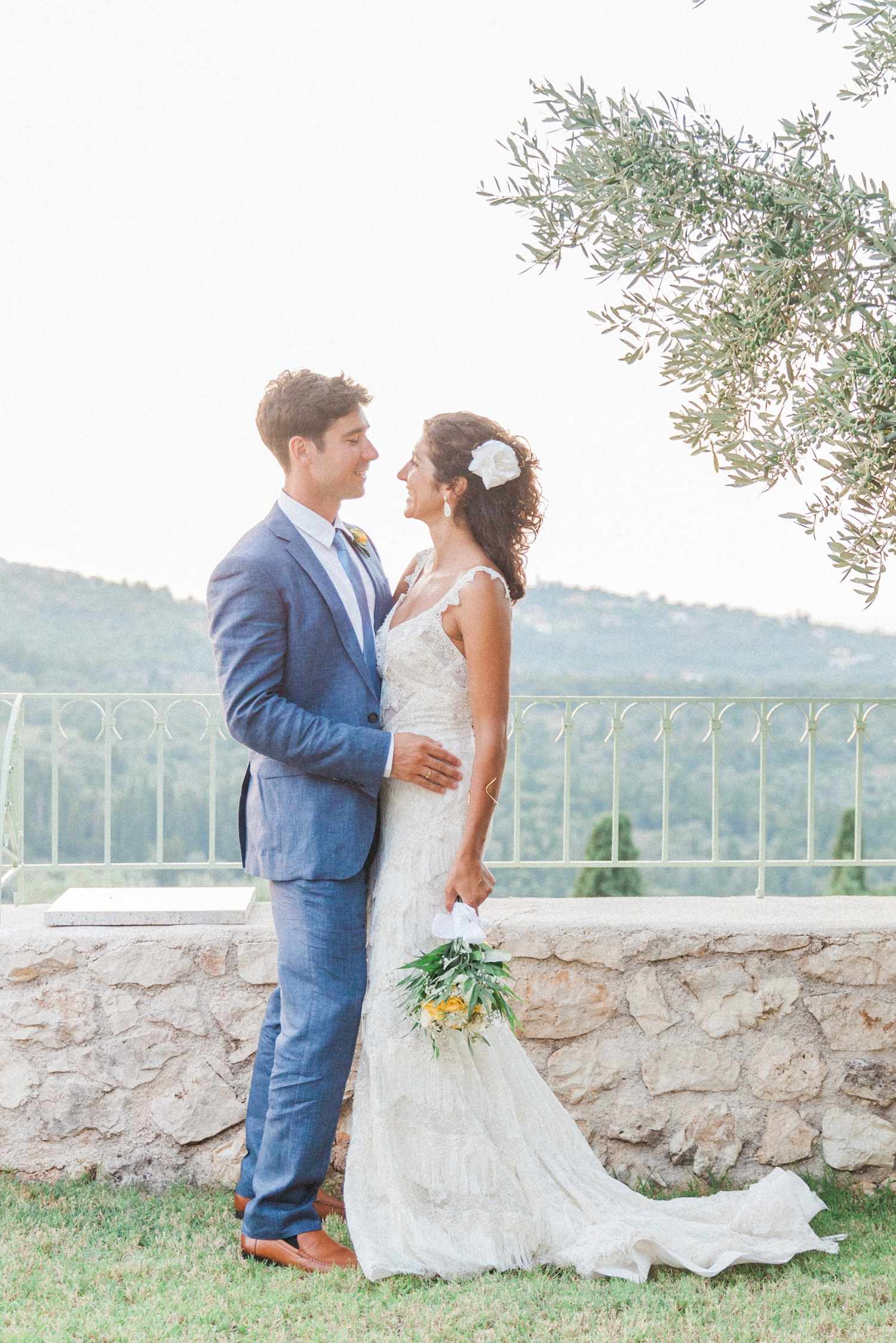 Bride and groom standing under an olive tree at their wedding in Ithaca, Greece