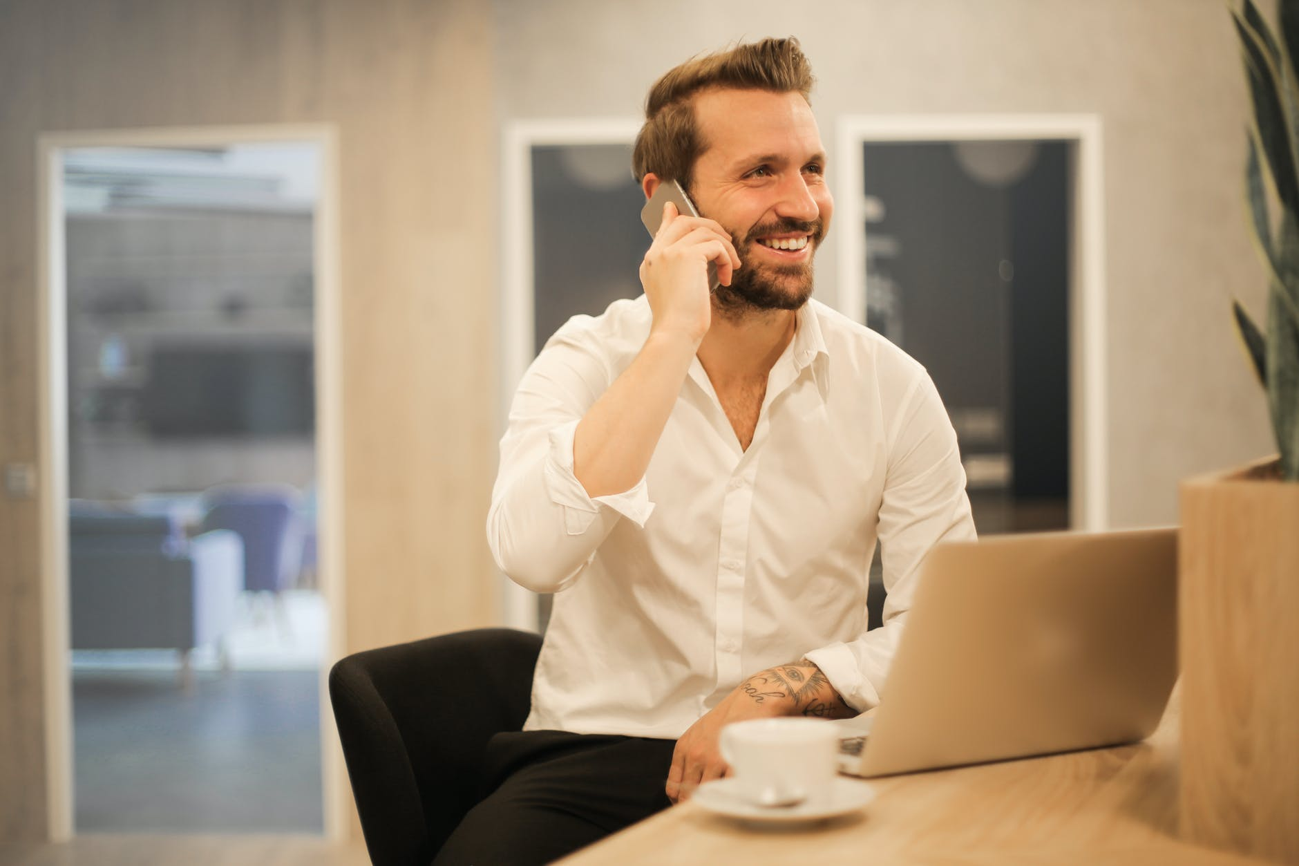smiling formal male with laptop chatting via phone