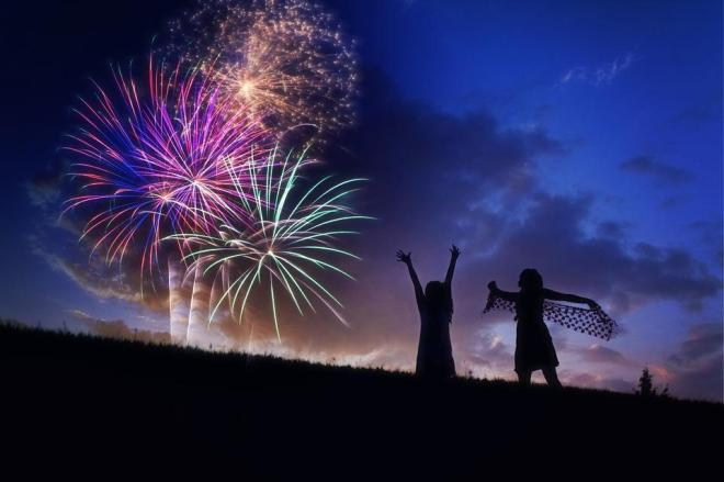 Magenta, cyan, and orange fireworks explode in a dark-blue cloudy sky. Silhouettes of two women celebrate on a slope.