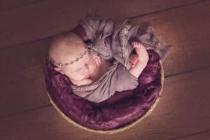newborn girl wrap in a basket