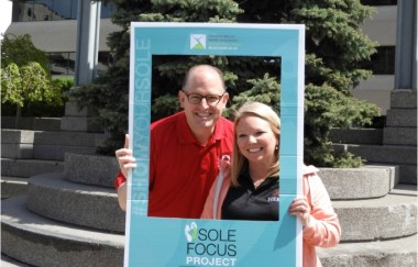 The Mayor and a woman posing for photo with Sole Focus frame