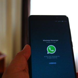 una persona sostiene un teléfono con la aplicación de WhatsApp abierta