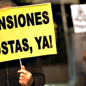 """Un pensionistas sostienen un Cartel """"Pensiones dignas ya"""""""