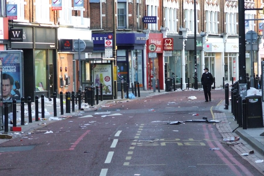 A police officer patrols St John's Road in Clapham Junction following a night of riots.