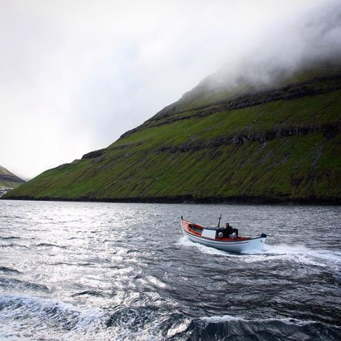 Misty mountains and rough seas, a boat sailing across the waves to Klaksvik, Faroe Islands