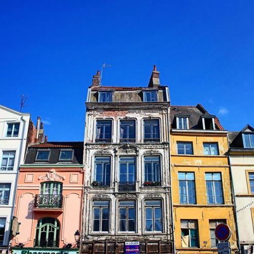 Beautiful architectural buildings in Lille, France, yellow and pink buildings, blue sky