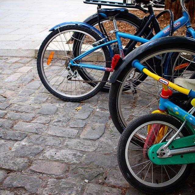 paris school parking lot, rows of bicycle wheels on brick bike rack, images of paris