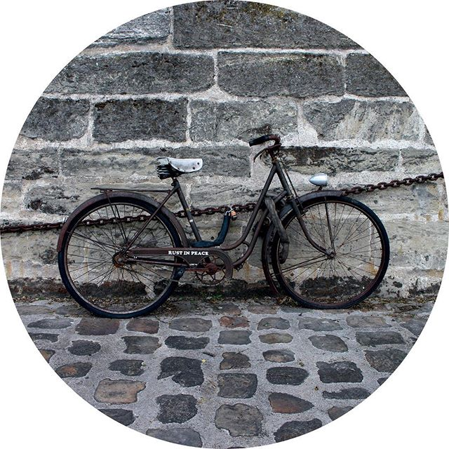 Rusty bicycle on a stone wall along Paris' Canal de l'Ourcq